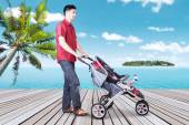 Man with his baby in stroller at pier — Stock Photo