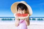 Child bites a watermelon at coast — Stock Photo
