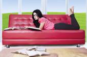 Female student on sofa with laptop and books — Stock Photo