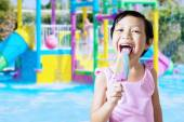 Girl licking an ice cream at pool — Stock Photo