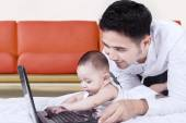 Male toddler playing laptop with his dad — Stock Photo