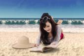 Pretty woman reading book on the beach — Stock Photo