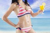 Sexy model with orange juice at shore — Stock Photo
