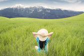 Woman enjoying mountain view on meadow — Stock Photo
