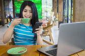 Woman reading message while enjoying coffee — Stock Photo