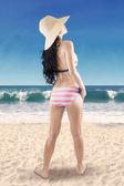 Woman standing on the coast with hat — Stock Photo