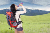 Woman with backpack drinks water at hill — Stock Photo