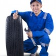 Young mechanic with tire showing thumb up — Stock Photo #72905317