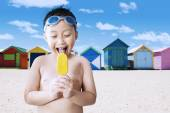 Happy little boy licking ice cream at shore — Стоковое фото
