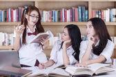 İki kız arkadaşlarının kitaplığındaki dinleme — Stok fotoğraf
