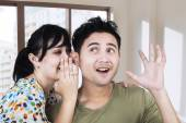 Woman whispering a news to her boyfriend — Stock Photo