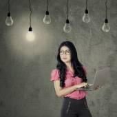 Worker with laptop looking at light bulb — Stock Photo