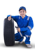 Young mechanic with tire showing thumb up — Stock Photo