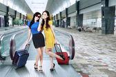 Modern girls standing in airport hall — Stock Photo