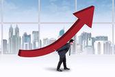 Businessman carrying an upward chart — Stock Photo