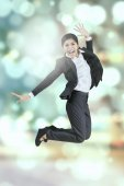 Businesswoman leaps with bokeh background — Stock Photo