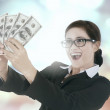 Woman with light glitter background holds money — Stock Photo #74070717