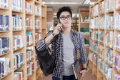 Trendy student talking on phone in library — Zdjęcie stockowe