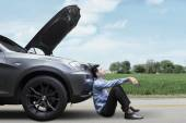 Man sitting on the road with broken car — Stock Photo