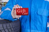 Workshop worker holds a gift card — Stock Photo