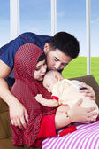Young muslim parents kiss their kid — Stock Photo