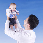 Dad lift up his baby under blue sky — Stock Photo