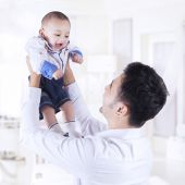 Father lift up male infant in the bedroom — Stock Photo