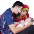 Muslim parents and baby on sofa — Stock Photo #75832679
