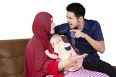 Two parents quarrel while holding a baby — Stock Photo