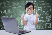 Child with laptop shows OK gesture in class — Stock Photo