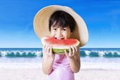 Cute girl with hat eating watermelon — Stock Photo