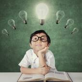 Little girl looking up bright lamp — Stock Photo