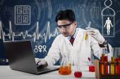 Scientist with laptop and chemical glassware — Stock Photo