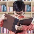 Adorable little student reads book in library — Stock Photo #77339184