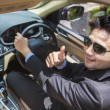 Successful man shows thumb up in new car — Stock Photo #77342566