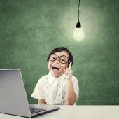 Creative kid with laptop pointing at lamp — Stock Photo