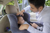 Father putting his baby on the car seat — Stock Photo