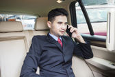 Male entrepreneur talking on the phone in car — Stock Photo