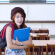 Friendly high school student smiling in class — Stockfoto #77707212