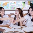 Group of modern students joining hands — Stock Photo #77707358