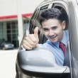 Young man shows thumb up in the car — Stock Photo #77709752