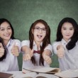Three high school students showing thumbs up — Stock Photo #78965486
