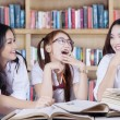 Joyful students talking and laughing in library — Stock Photo #78965638