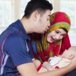 Young parents with newborn baby on sofa — Stock Photo #78968484