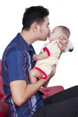 Adorable baby kissed by his dad — Stock Photo