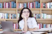 Lovely schoolgirl with glasses daydreaming in library — Stock Photo
