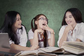 Lovely schoolgirls talking in the class — Stock Photo