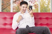 Man reading message with cellphone on sofa — Stock Photo