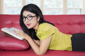 Cute woman reading book on sofa while smiling — Stock Photo
