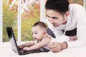 Curious baby with dad playing laptop — Stock Photo
